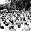 A large crowd wearing white sitting on the Plaza of the America during a Vietnam War protest in 1972