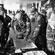 Military personnel hover around a map