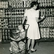 woman shopping in Canal Zone commissary with baby in shopping cart